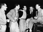Actor Robert Taylor, seated on a chest, talks with his colleagues Eleanor Parker, Ricardo Montalban, Jonathan Cott and James Whitmore