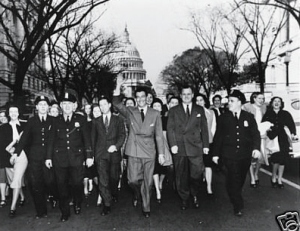 Robert Taylor walks down the street after leavings the hearings, accompanied by a crowd of admirers.