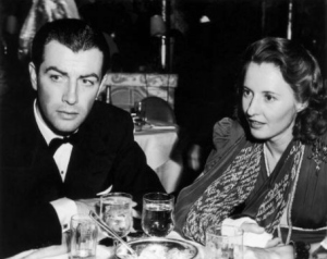 Married American actors Robert Taylor (1911-1969) and Barbara Stanwyck (1907-1990) sit at a table in a restaurant, wearing formal attire.  Stanwyck wears a cast on her forearm and uses a printed scarf as a sling.