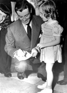 Robert Taylor signs an autograph for a little girl after leaving the HUAC hearings.
