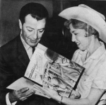 Taylor receives a gift of Nebraskaland Stamps from Jan Schenck of the Information and Tourism Division of the Nebraska Division of the Nebraska Game and Parks Commission on October 25, 1963. (Omaha World Herald)