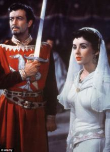 Neither a cloak nor a beard can dim the luster of the Taylors, Liz and Bob, who co-star in MGM's Ivanhoe.