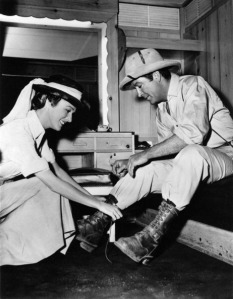 Actress Eleanor Parker, on her kneels, helps Robert Taylor, dressed up as an archaeologist, to lace up a boot on the set of the movie 'Valley of the Kings'. Egypt, 1954. (Photo by Mondadori Portfolio via Getty Images)