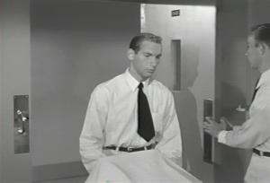 "Ralph Moratz pushing a stretcher in ""Not as a Stranger."""